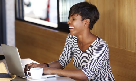 Smiling young african american woman using laptop
