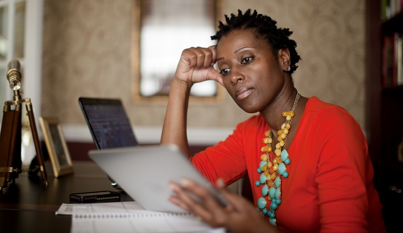 African-American woman sitting at desk in home office looking at ipad tablet
